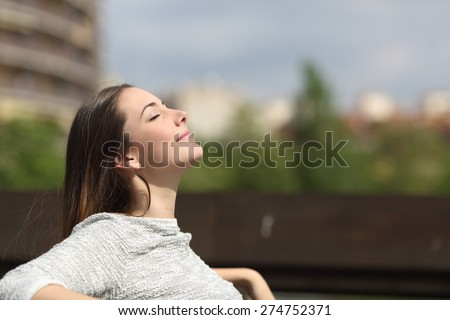 Urban woman sitting on a bench of a park and breathing deep fresh air #274752371