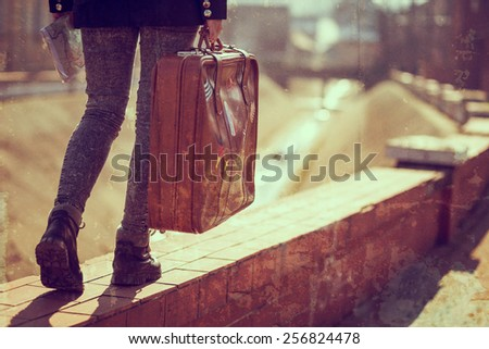 Urban young girl, walking down the street, carrying suitcase and a map.