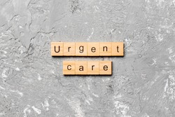 Urgent care word written on wood block. Urgent care text on cement table for your desing, concept.