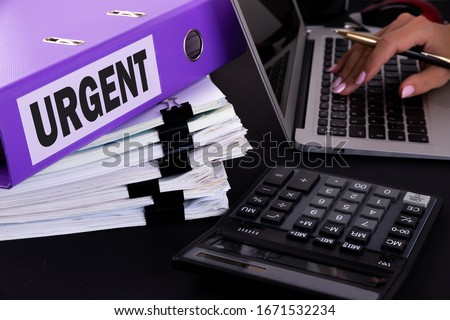 Urgent Situation Necessary Imperative Important Concept. A business woman is surrounded by large bundles of documents. Above is a purple folder with the words URGENT.