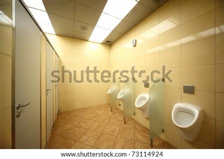 urinals and doors in public restrooms, yellow tiles on floor and walls