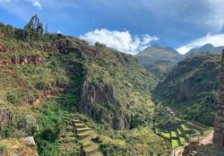 Urubamba Sacred Valley Incas Urubamba near Pisac town. Ancient Inca fortress ruin. Andes mountains view. Green grass agricultural terraces on mountain. Historical landscape burial place of noble Incas