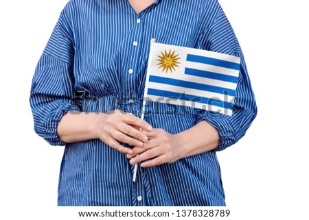 Uruguay flag. Close up of woman's hands holding a national flag of Uruguay isolated on white background. #1378328789