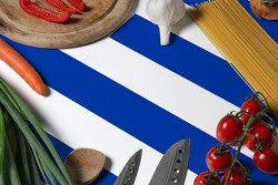 Uruguay flag on fresh vegetables and knife concept wooden table. Cooking concept with preparing background theme.