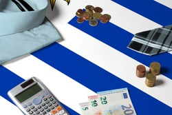 Uruguay flag on minimal money concept table. Coins and financial objects on flag surface. National economy theme.