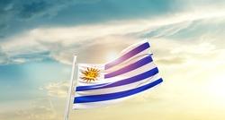 Uruguay national flag waving in beautiful clouds.