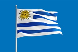 Uruguay national flag waving in the wind on a deep blue sky. High quality fabric. International relations concept.