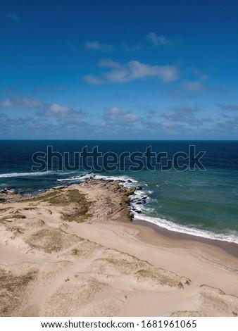 Uruguay, Punta del diablo. Vista aérea de la playa y el mar. Las olas rompen contra la arena y rocas, el agua es verde y oscura.  Uruguay tiene estas playas salvajes y solitarias. Zdjęcia stock ©