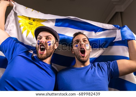 Uruguayan fans holding the national flag - Shutterstock ID 689982439
