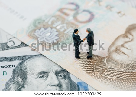 US and China financial tariff trade war negotiation talk, collaboration or discuss concept, miniature people businessman leader handshaking on Chinese yuan banknotes and US dollar. #1059309629
