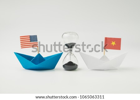 US and China financial trade war tariff strategy concept, hourglass / sandglass at the center between blue paper ship with America flag and white one with China flag.