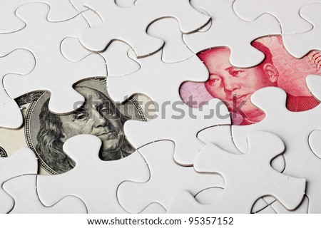 US and Chinese currencies as part of a jigsaw puzzle  - stock photo