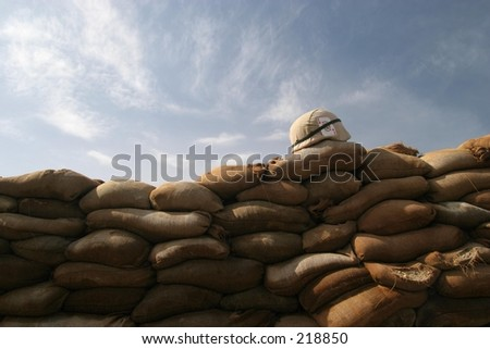 US Army Helmet on sandbag bunker. - stock photo