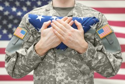 US Army soldier holding folded USA flag before his chest