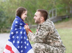 US army soldier with daughter and USA flag in park