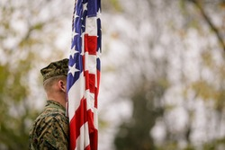 US Army soldier with US flag at a military parade