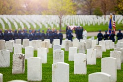 US burial procession with soldiers and flag on background on military cemetery
