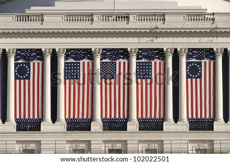US Capitol Building with American flags draped between columns - stock photo
