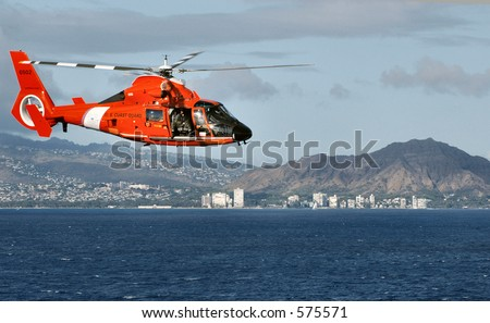 US Coast Guard helicopter flying past Diamond Head crater on island of Oahu, Hawaii.