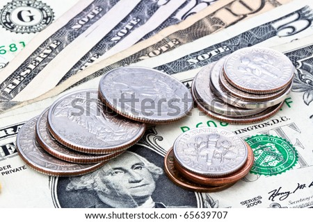 US Currency with one dollar coins sitting on one five ten and fifty dollar notes