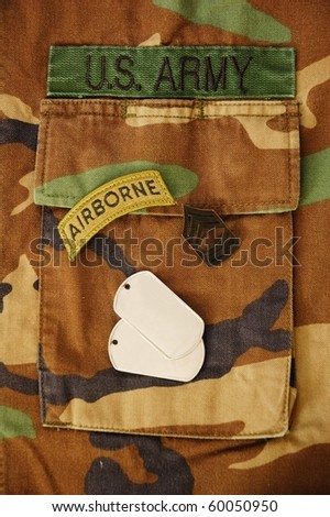 US dog tags, airborne patch and rank on woodland camo pocket background