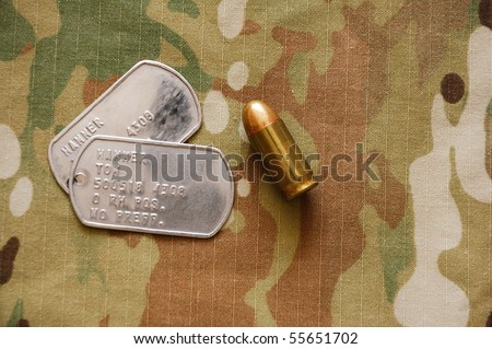 US dog tags and .45 caliber cartridge on multicam background