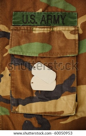 US dog tags on woodland camo pocket background - stock photo