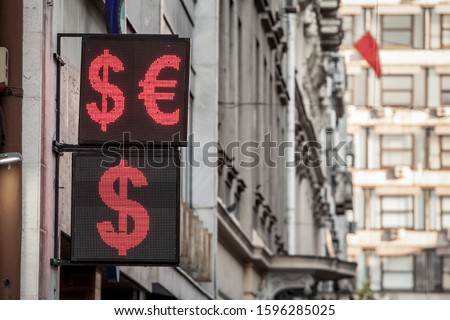 US Dollar and Euro currency symbols on display in front of an exchange office. Abbreviated EUR and USD, these currencies are among the most traded money in the world.