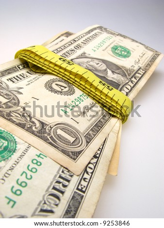 US dollar banknotes wrapped into measurement ruler on light background