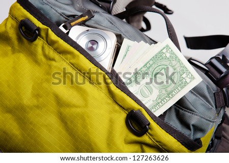 US dollar bills and compact camera in packed backpack