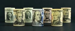 US dollar bills of various denominations in circulation lined up on a black background.