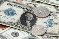 US dollar from 1923 next to half dollar coins. Dollar background. US currency evolving over time, large one USD banknote on top of new dollar bills