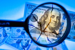 US dollar under a magnifying glass. Concept - checking state of US economy. Crack on dollars as a symbol of financial problems. Problems in economy revealed by audit. Problems caused by US crisis.