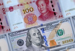 US 100 dollars bills and Chinese currency yuan banknotes closeup background. USA China business finance economic trade tension conflict, America China economies trade war, financial crisis concept
