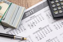 Us Dollars, calculator, pen and calendar.