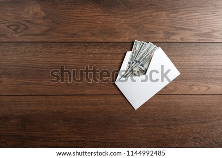 US dollars in a white envelope on a wooden table. The concept of income, bonuses or bribes. Corruption, salary, bonus.