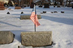 US flag at gravestone at small Chicago suburban cemetery in winter with snow