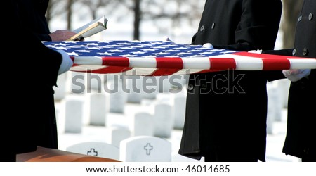 US Flag being held over casket at Arlington National Cemetery
