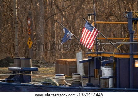 US Flag Flipping over a Blue Barge Docked at Lock 20 in Erie Canal.