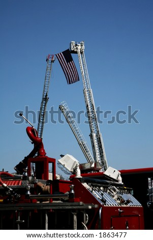 US Flag held up between two firetruck ladders in the sky