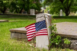 US flag on grave in cemetery