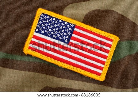 US flag patch on woodland camo background