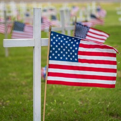 US flag with cross in cemetery
