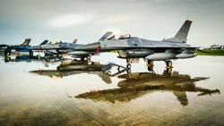 US jet fighters on display at airshow and reflected on flight line after heavy rain