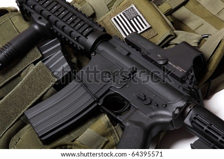 US military concept. Tactical vest with U.S. flag and M4 RIS assault carbine close-up. Studio shot.