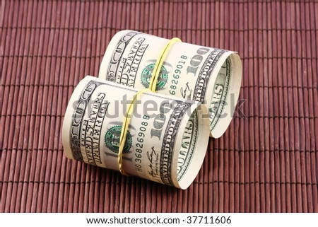 US paper currency bills rolled up and tied with a yellow rubber band
