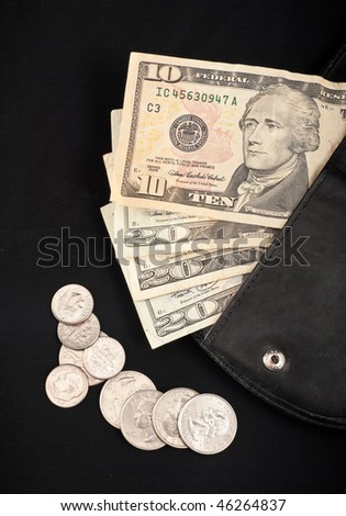 US Paper Currency in Wallet with Scattered Coins on Black