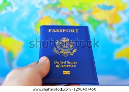 US passport in hand on world map background #1298407450