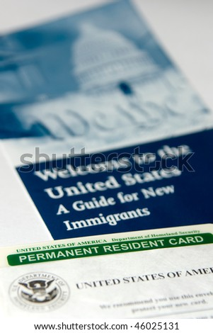 US permanent resident card (Green Card) seen with welcome to the USA brochure