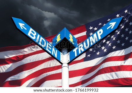 Photo of  US presidential race. The names of Presidents Donald Trump and Joe Biden on the roadside sign on the background of the American flag and a stormy sky